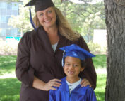 Young woman and child in graduation cap and gowns
